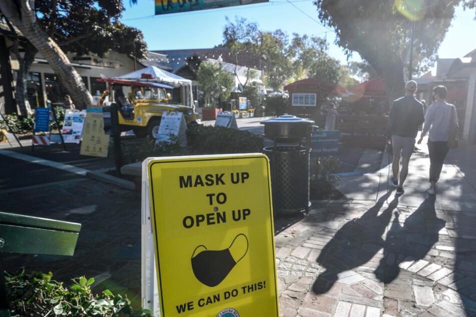 Laguna Beach: Ein Schild weist Besucher der Forest Avenue in Kalifornien darauf hin, eine Maske zu tragen. Kalifornien führt wegen steigender Corona-Zahlen wieder härtere Maßnahmen im Kampf gegen die Pandemie ein.