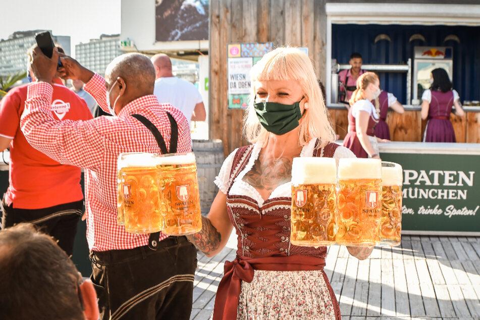 """Eine Bedienung trägt Biergläser bei einer Festveranstaltung mit dem Titel """"Wiesn da oben""""."""