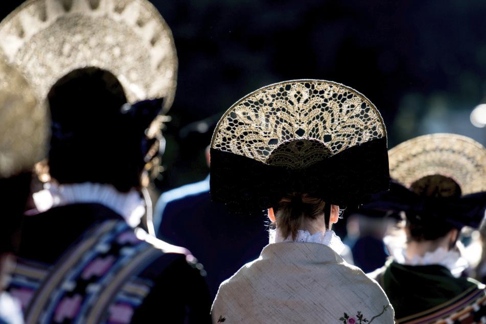 Die prächtigen Kopfbedeckungen der Radolfzeller Trachtenträgerinen sind in Radolfzell nach der Mooser Wasserprozession im Gegenlicht zu sehen. (Archivbild)
