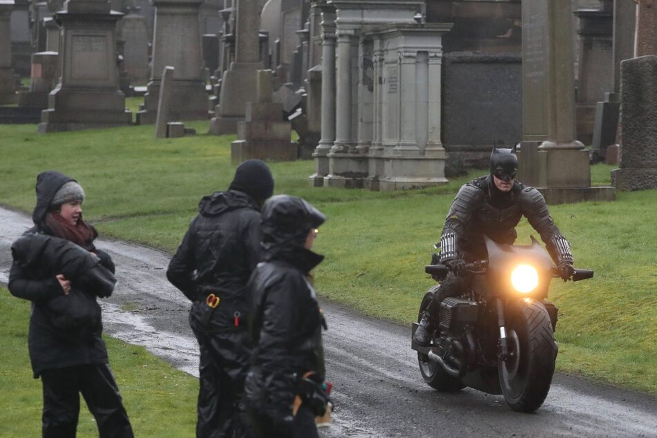 Batman riding his motorcycle through Glasgow Necropolis cemetery during filming.