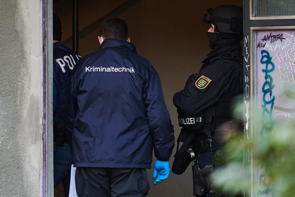 Polizei und Kriminaltechniker am Eingang eines Wohnhauses in Berlin.