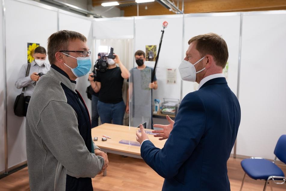 Der Ministerpräsident (r.), hier bei einem Besuch im Impfzentrum von Löbau, ist selbst bereits doppelt gegen Covid-19 geimpft.