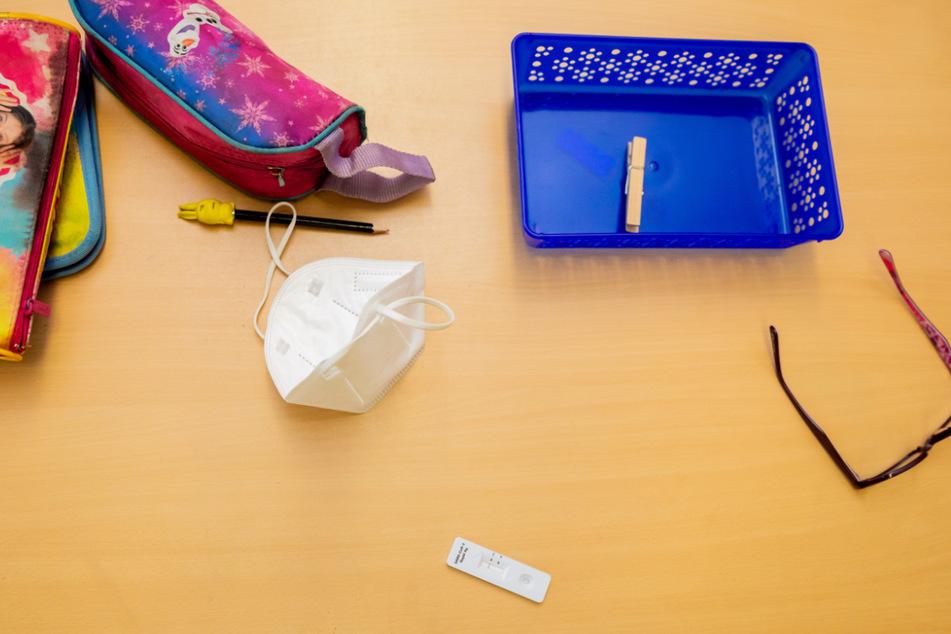 Ein Schnelltest, eine FFP2-Maske sowie Schulmaterialien liegen auf einem Tisch. Weil die verbindliche Testpflicht scheiterte, bleiben die Schulen im Kreis Gotha weiter geschlossen. (Symbolbild)