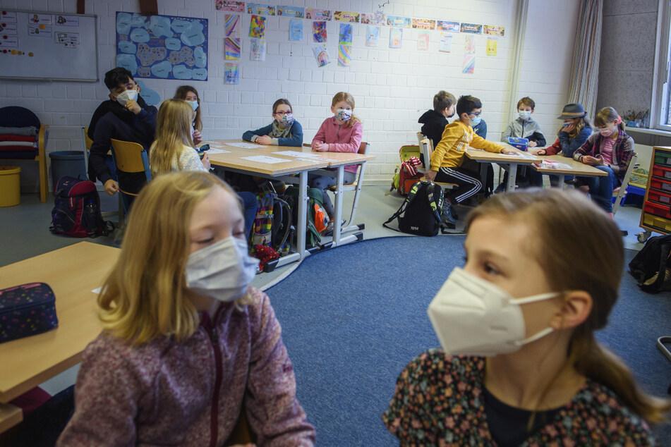 Schüler und Schülerinnen einer 4. Klasse sitzen im Unterricht an einer Grundschule zusammen an einem Tisch und tragen dabei einen Mund-Nasen-Schutz. In Thüringen wird die Maskenpflicht ab kommenden Montag für alle Klassenstufen gelten.