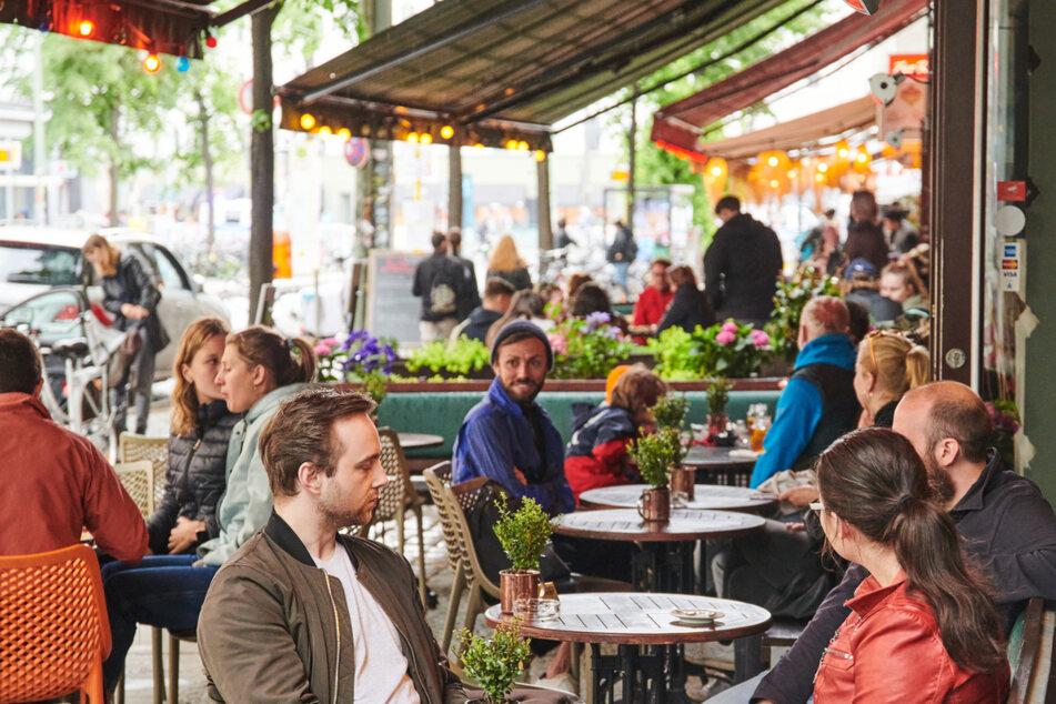 Viele Gäste sitzen zur Mittagszeit in Restaurants und Cafés im Berliner Weinbergsweg.