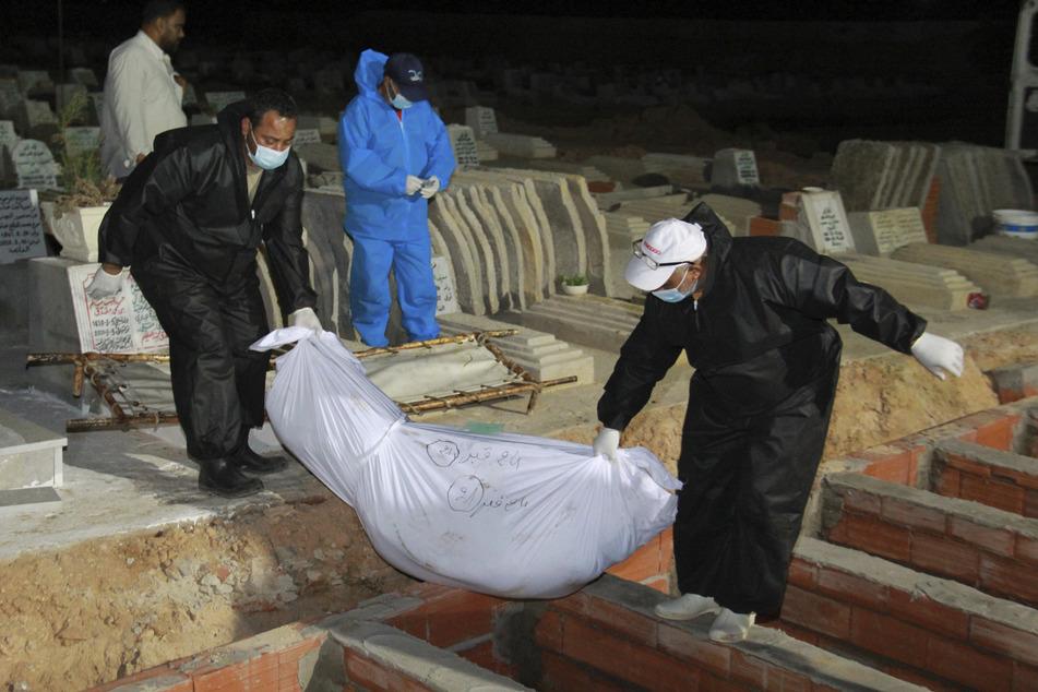 Pfleger begraben einen Migranten auf einem Friedhof, der bei dem Unglück ums Leben kam.