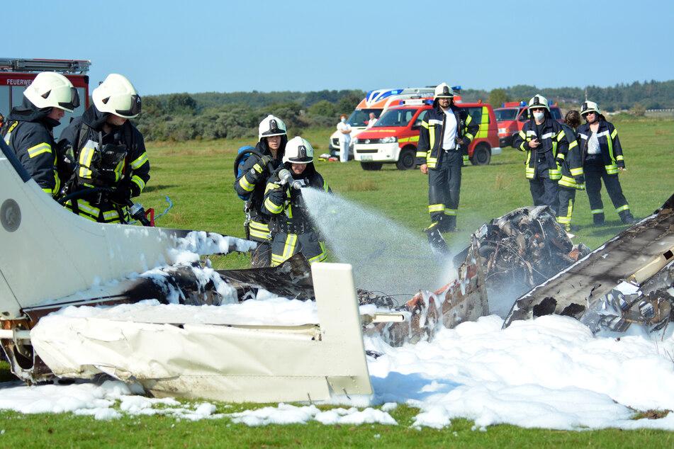 Borkum: Feuerwehrleute löschen das in Brand geratene Flugzeug.