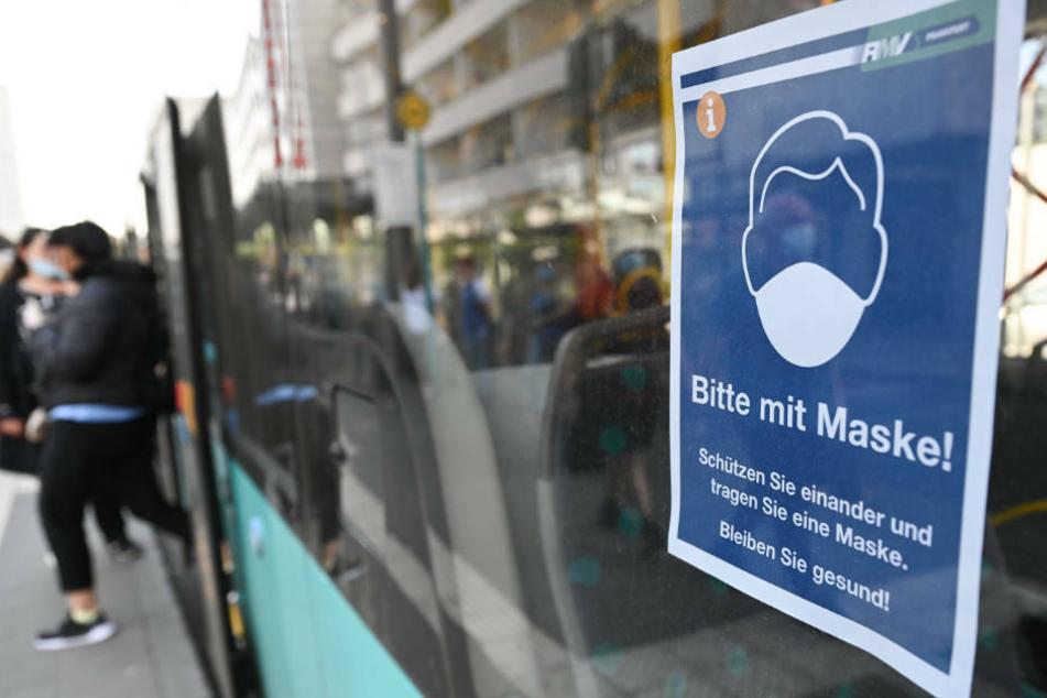 """Ein Plakat mit der Aufschrift """"Bitte mit Maske! Schützen Sie einander und tragen Sie eine Maske. Bleiben Sie gesund!"""" ist an der Haltestelle Konstabler Wache in einem Bus des Rhein-Main-Verkehrsverbunds angebracht."""