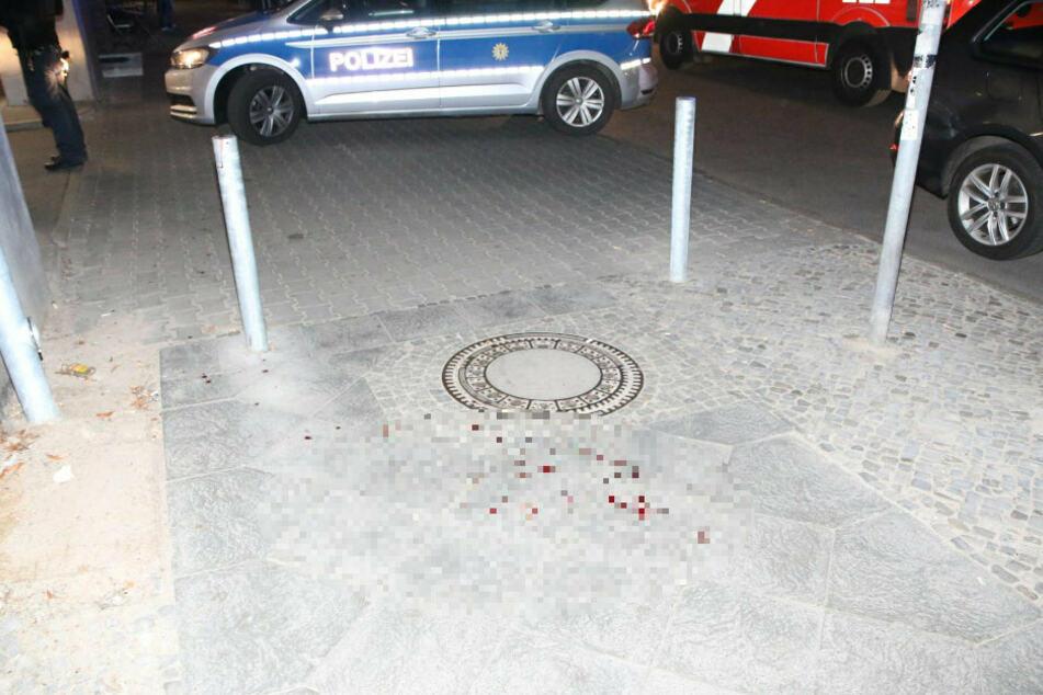 Blut ist neben einem Gullydeckel auf dem Bürgersteig zu sehen.