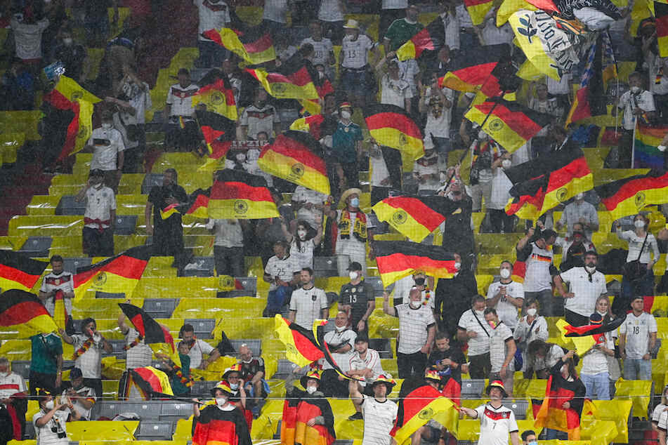 Deutsche Fans feuern unter starkem Regen ihre Mannschaft in München an.