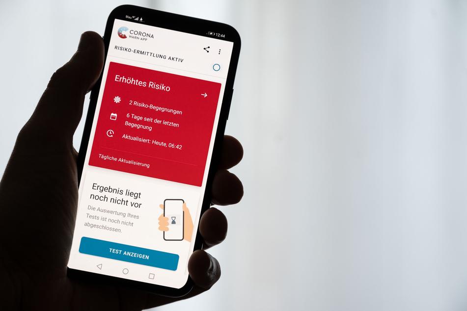 Ein Mann hält ein Smartphone in der Hand, auf dem die Corona-Warn-App der Bundesregierung ein erhöhtes Risiko anzeigt (gestellte Szene).