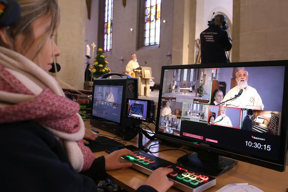 Eine Frau steuert den live übertragenen Internet-Auftritt der Ostermesse von Bischof Gerhard Feige aufgrund der Maßnahmen gegen das neuartige Coronavirus aus der römisch-katholischen Kathedralkirche Sankt Sebastian.