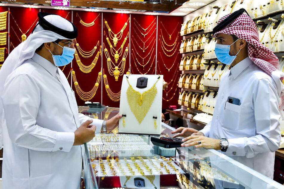 Männer mit medizinischem Mundschutz unterhalten sich einem Goldgeschäft in Doha.