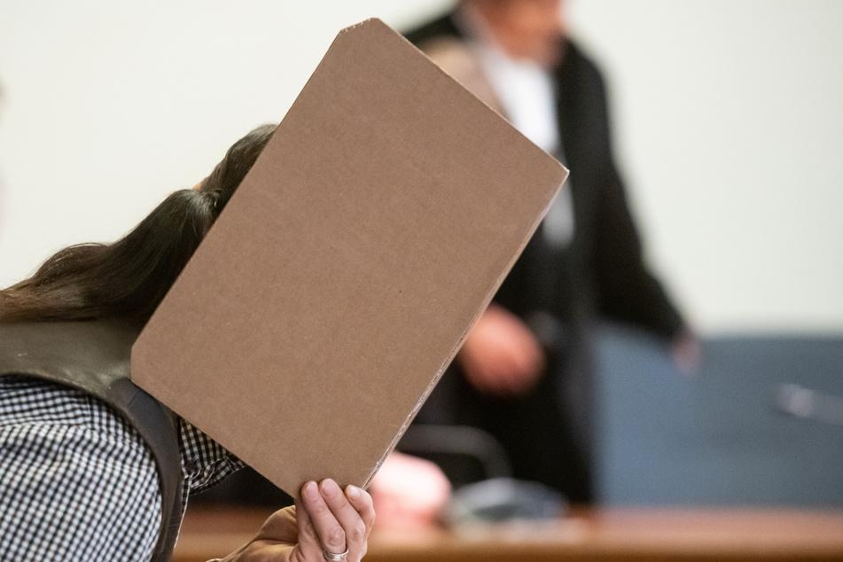 Der Angeklagte sitzt im Landgericht auf der Anklagebank und verbirgt sein Gesicht.