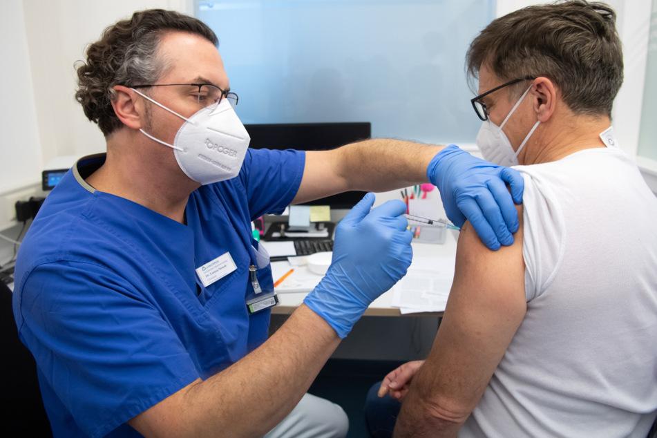 Ein Arzt der Asklepios Klinik impft einen Kollegen gegen das Coronavirus. Die Impfquote an Bayerns Kliniken liegt laut Krankenhausgesellschaft mittlerweile über 90 Prozent.
