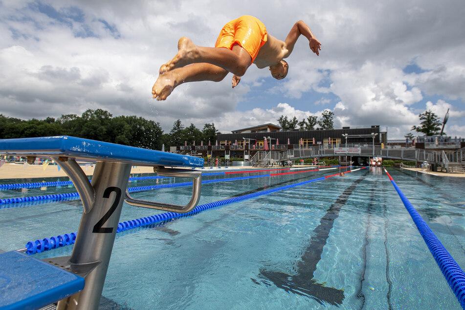 Ein Besucher springt im Schwimmbad vom Startblock.