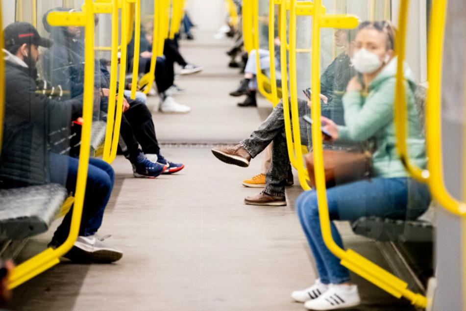 Fahrgäste sitzen in einer U-Bahn, wobei eine Frau einen Mundschutz trägt. (Archivbild)