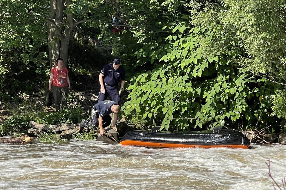Polnische Polizisten untersuchen das gekenterte Schlauchboot auf der Neiße.