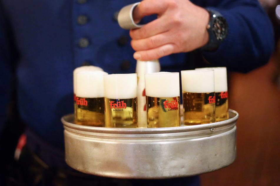 Ein Köbes (Kellner) trägt Kölsch-Bier aus.