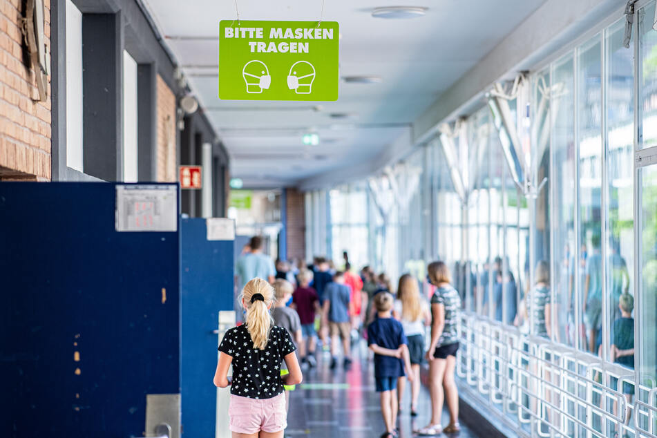 """Auf dem Flur einer Gesamtschule, hängt ein Schild mit der Aufschrift: """"Bitte Masken tragen""""."""