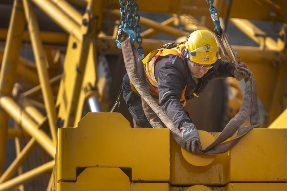 Ein Arbeiter befestigt die Gegengewichte des Krans.