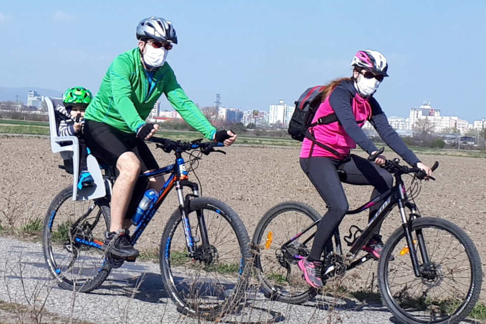 Corona-Krise: Radfahrer sind mit Mundschutz auf einer Straße unterwegs.
