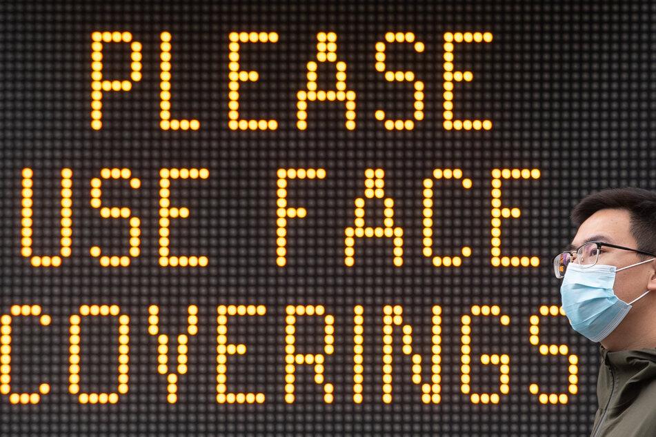 Ein Mann mit Mundschutz geht in der Nähe der Tower Bridge an einer Anzeige vorbei, die die Menschen bittet einen Gesichtsschutz zu benutzen. (Archivbild)