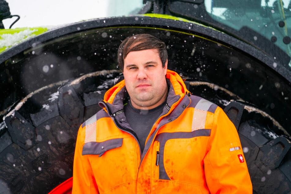 Der Landwirt Christian Bezold steht bei dichtem Schneefall vor seinem Traktor.