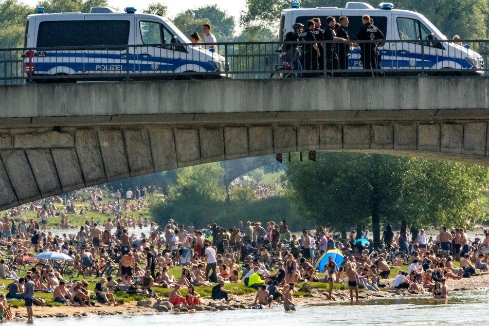 Hunderte Menschen belagern bei sommerlichen Temperaturen die Frühlingsanlagen an der Isar. Auf der Reichenbachbrücke im Vordergrund stehen Einsatzwagen der Polizei.
