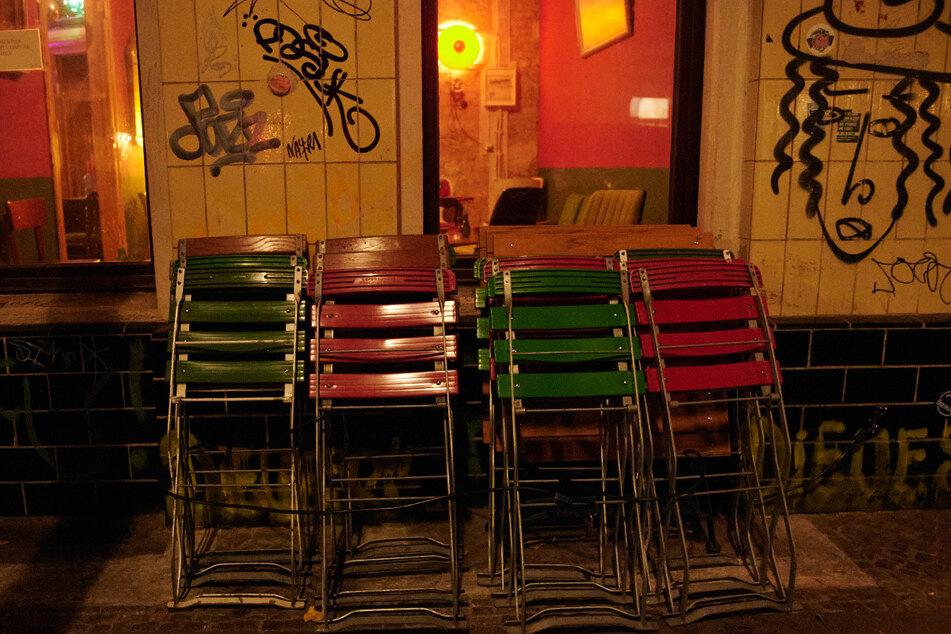 Kurz nach der Sperrstunde stehen zusammengeklappte Stühle vor einer Bar in Berlin-Neukölln. Wegen der Corona-Pandemie gelten eine nächtliche Sperrstunde und strengere Kontaktverbote für drinnen und draußen.