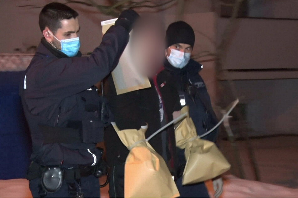 Zwei Polizisten führen einen Tatverdächtigen ab, dessen Hände zur Spurensicherung mit Papiertüten umwickelt wurden.