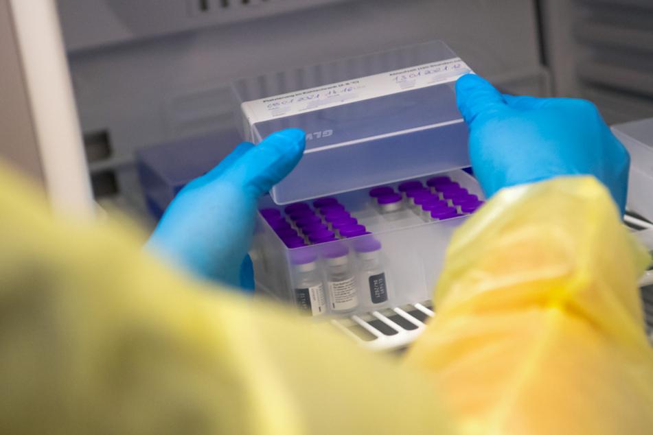 Eine Mitarbeiterin vom bayerischen roten Kreuz (BRK) holt Ampullen des Impfstoffs von Biontech/Pfizer gegen das Coronavirus SARS-CoV-2 im Impfzentrum aus einem speziellen Kühlschrank.