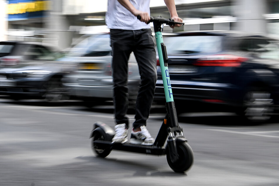 Ein Mann fährt mit einem E-Tretroller des Anbieters Tier.