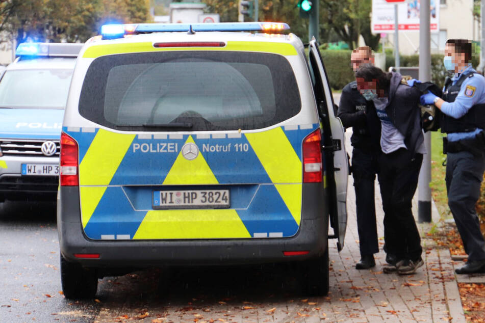 Nach Biss-Attacke in Hanau: Der mutmaßliche Täter wurde festgenommen und von zwei Polizisten abgeführt.