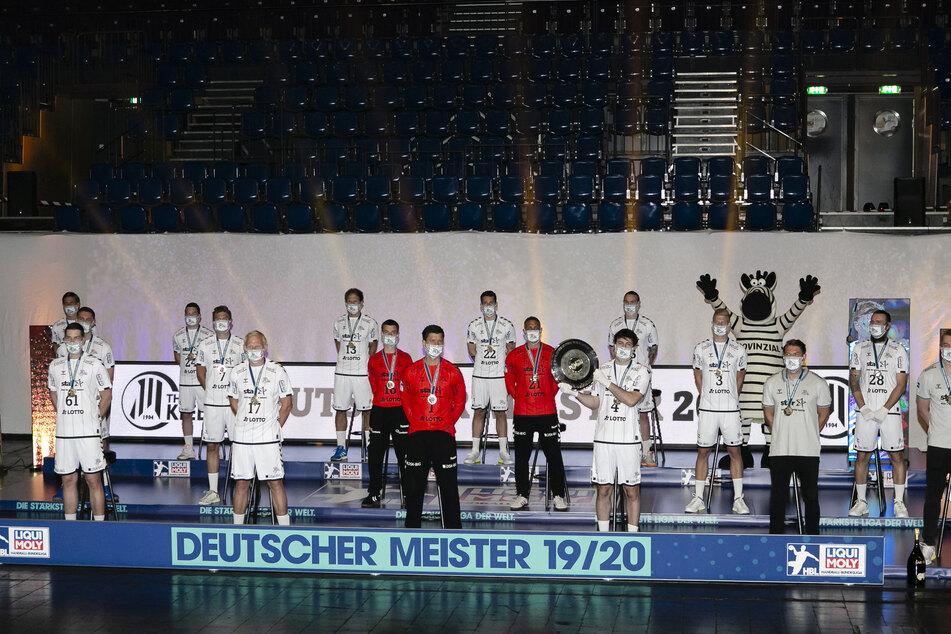 Die Spieler des THW Kiel stehen nach der Ehrung zum deutschen Handballmeister mit Abstand und Mund-Nase-Schutz auf einem Podest.