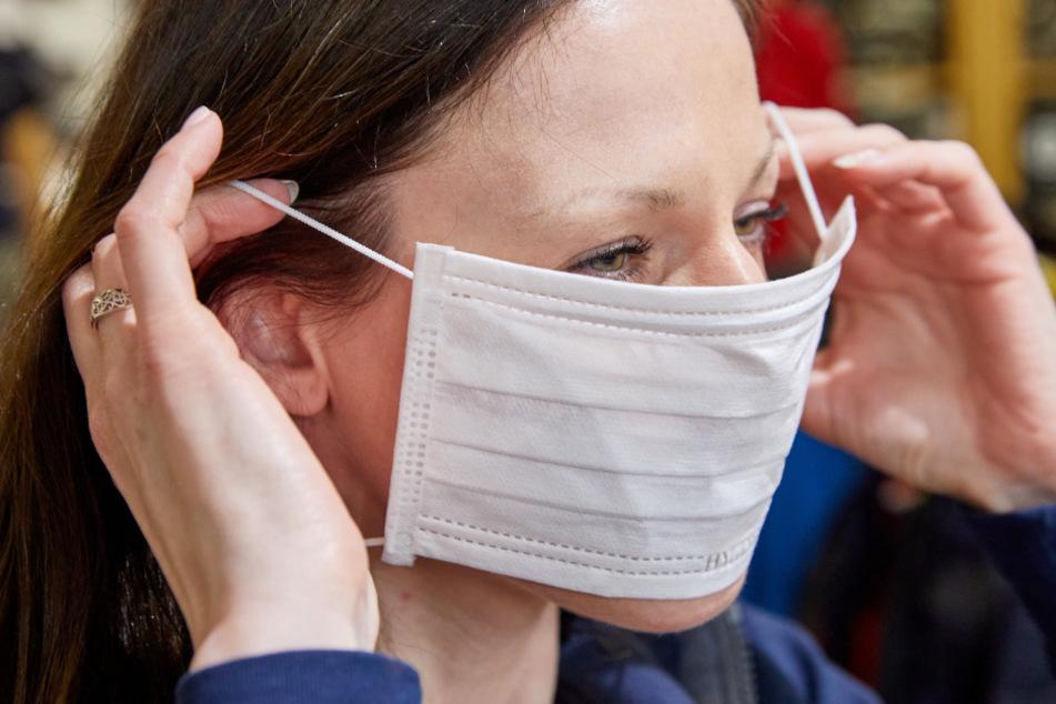Eine Frau zieht einen Mundschutz auf.