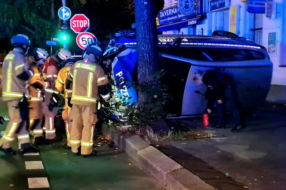 Feuerwehrleute kümmern sich um den verunglückten Polizeiwagen.