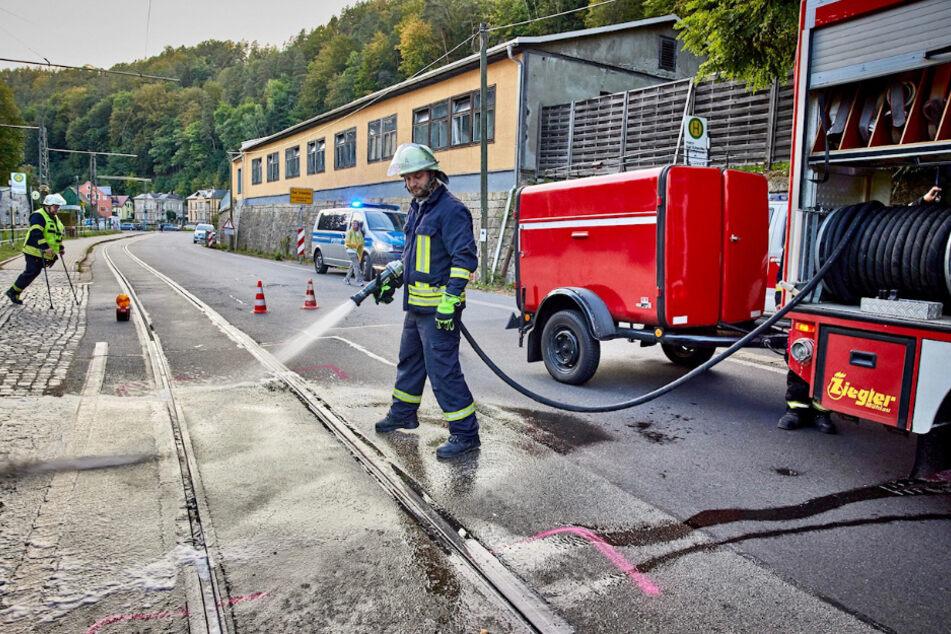 Ein Feuerwehrmann reinigt die Fahrbahn.