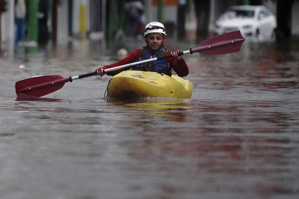 Eine Person paddelt in seinem Kajak auf einer überfluteten Straße in Tula.
