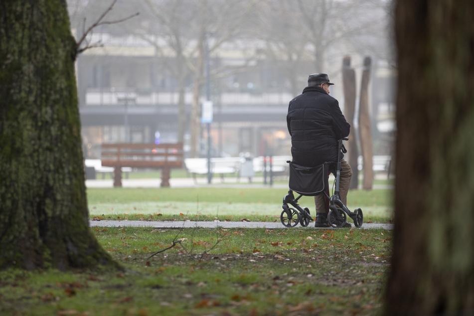 Ein älterer Mann sitzt auf seinem Rollator im Kurpark des Kurortes Bad Rothenfelde.