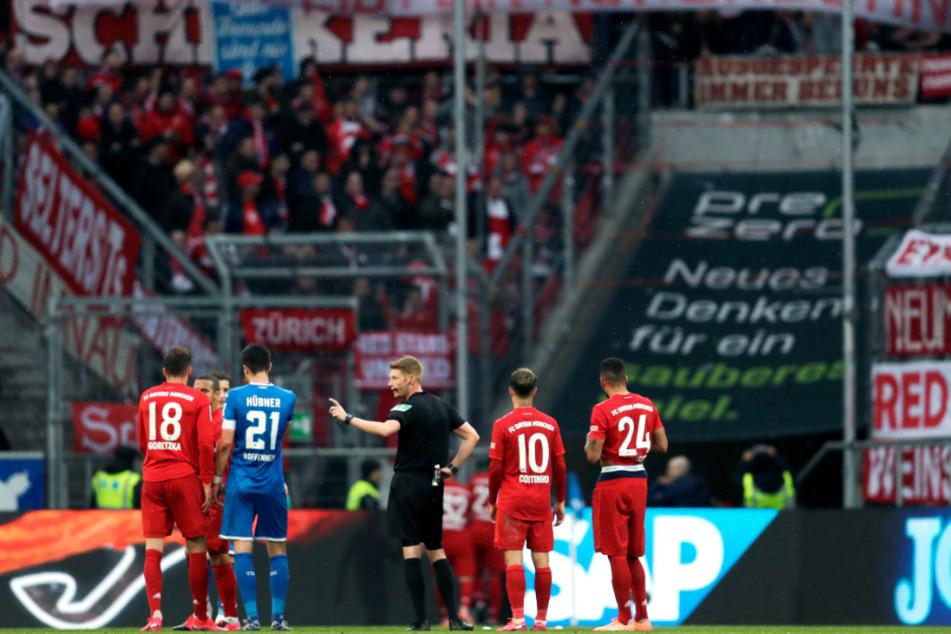 """Schiedsrichter Christian Dingert (M) spricht mit Spielern von Hoffenheim und München, während die Münchner Fans auf der Tribüne ein Banner mit der Aufschrift """"Hopp bleibt ein Hurensohn"""" zeigen."""