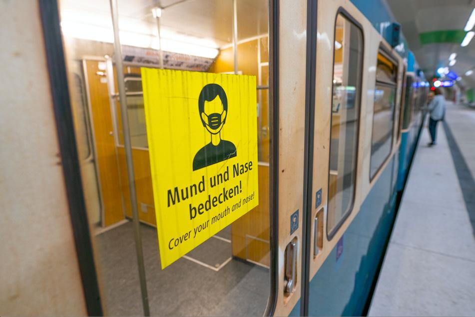 """""""Mund und Nase bedecken!"""" steht in Deutsch und Englisch auf einem Schild an einem Waggon der Münchner U-Bahn."""