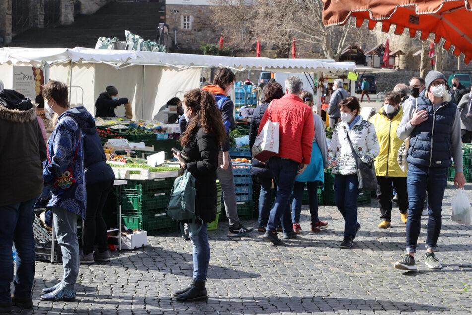 Menschen warten mit Abstand an einem Gemüsestand auf dem Erfurter Domplatz, wo der wöchentliche Markt stattfindet. In Thüringen ist die Inzidenz gesunken. Drei Städte haben inzwischen einen Wert von unter 100.