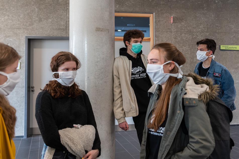 Abiturienten am Gymnasium Dresden Klotzsche stehen vor Beginn der Konsultationen im Treppenhaus und tragen einen Mundschutz.