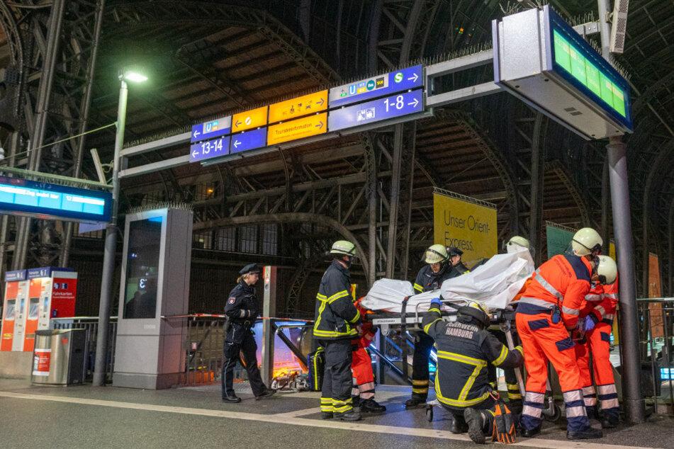Einsatzkräfte transportieren den Leichnam ab.