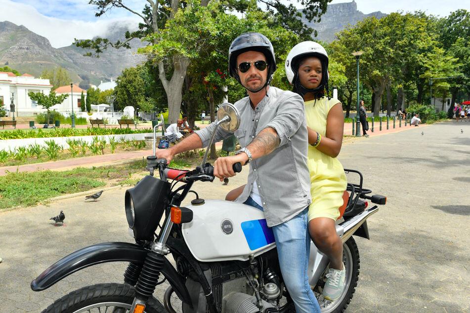 """Kapitän Max Parger (Florian Silbereisen) und Lea Bremer (Melodie Wakivuamina) sitzen auf einem Motorrad - eine Szene aus """"Das Traumschiff: Kapstadt""""."""