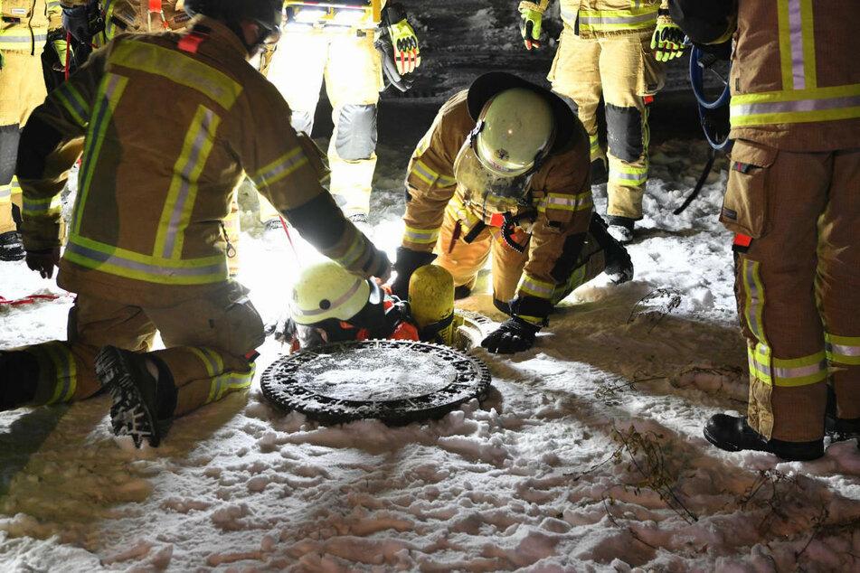 Ein Feuerwehrmann begibt sich zur Abdichtung des entstandenen Lecks in die Kanalisation.
