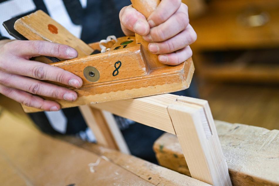 Ein Auszubildender im Schreiner-Handwerk arbeitet an einem Werkstück.
