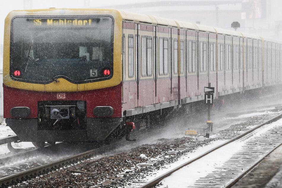 Eine S-Bahn der Linie S5 fährt an einem Bahnhof durch den Schnee. (Symbolbild)