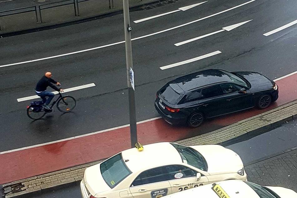 Ein Autofahrer am Neumarkt parkt auf dem mit einer durchgezogenen Linie abgetrennten Radstreifen. Ein Radfahrer muss ausweichen.